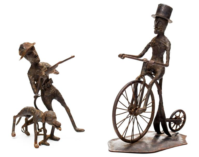 Fabulous pair of hand-forged iron sculptures from a black smith, circa 1900s of man on a bicycle with a cigar and a hunter with his dog, bird and gun. The bicyclist sits on a iron base. From an incredible art filled Philadelphia estate. Outsider art