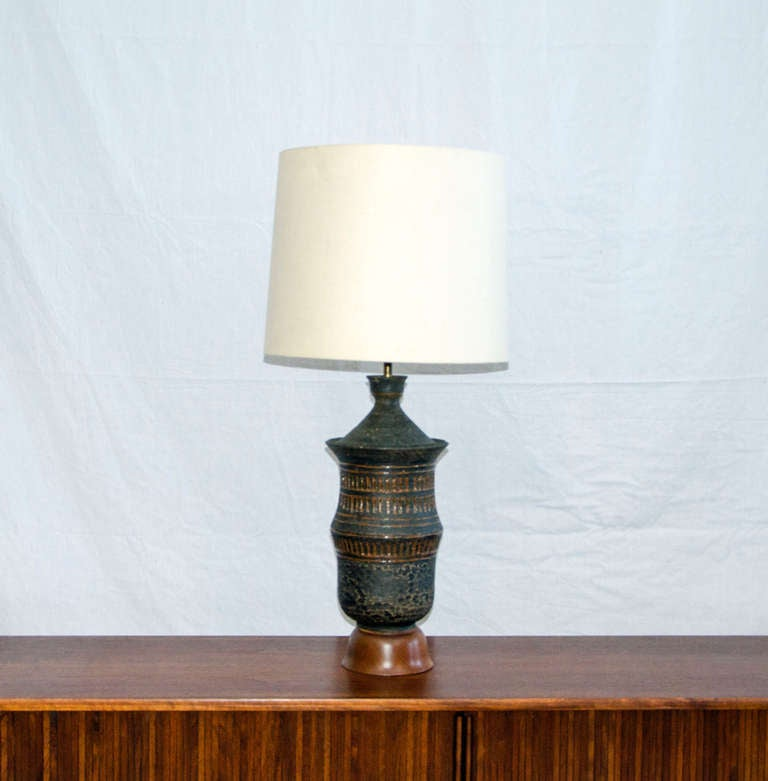 Table lamp with a stoneware base on a wooden pedestal base. Dark grey with lighter brown incised accents.