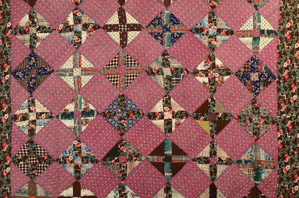 This Texas Puzzle quilt is made from a variety of exquisite printed wool challis fabrics. The back consists of seven alternating narrow and wide Bars of equally beautiful challis prints, making the quilt totally reversible. It is very light in