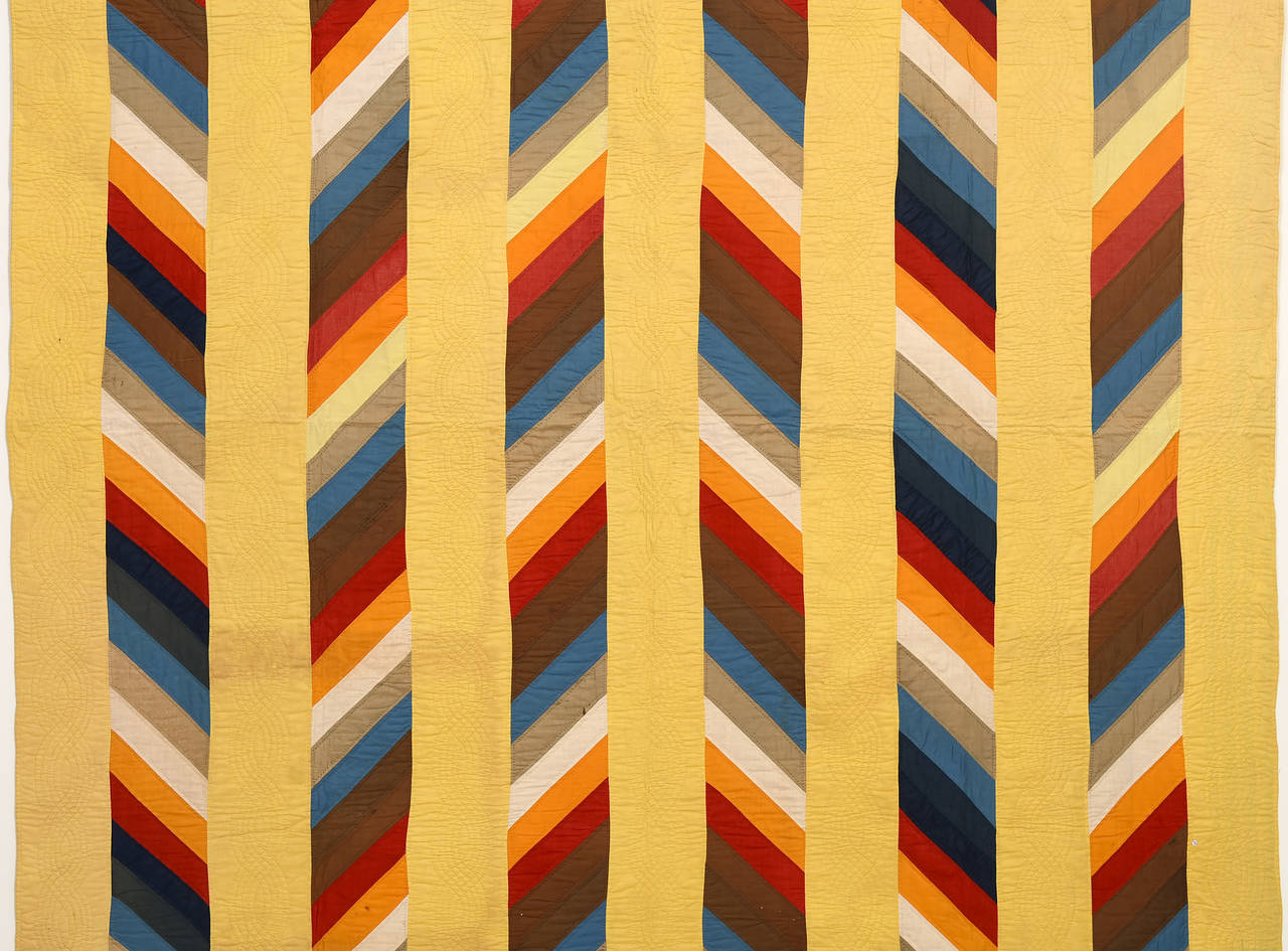 It is safe to say that this stunning version of a Joseph's Coat quilt is an original. The diagonal stripes form a three dimensional looking herringbone pattern that I have never seen. The yellow bars are all quilted with cable patterns. It is in