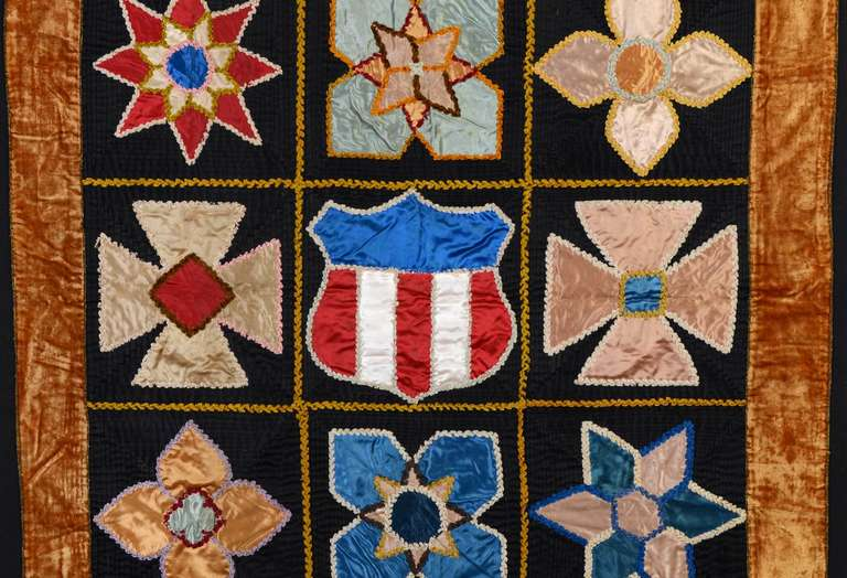 The construction of this Patriotic Crib Quilt  is as unusual as the combination of motifs. Each of the black background areas is actually made of thin strips of satin (about 1/4