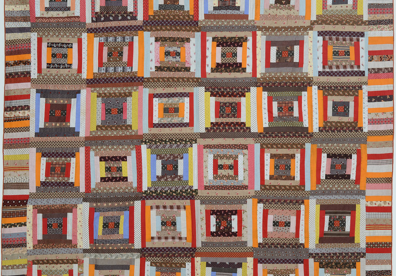 Classic courthouse steps log cabin quilt with a good use of lights and darks. Solid red and orange logs play well against the printed fabrics. Excellent condition. It is lightweight with no batting. Measurements are 78