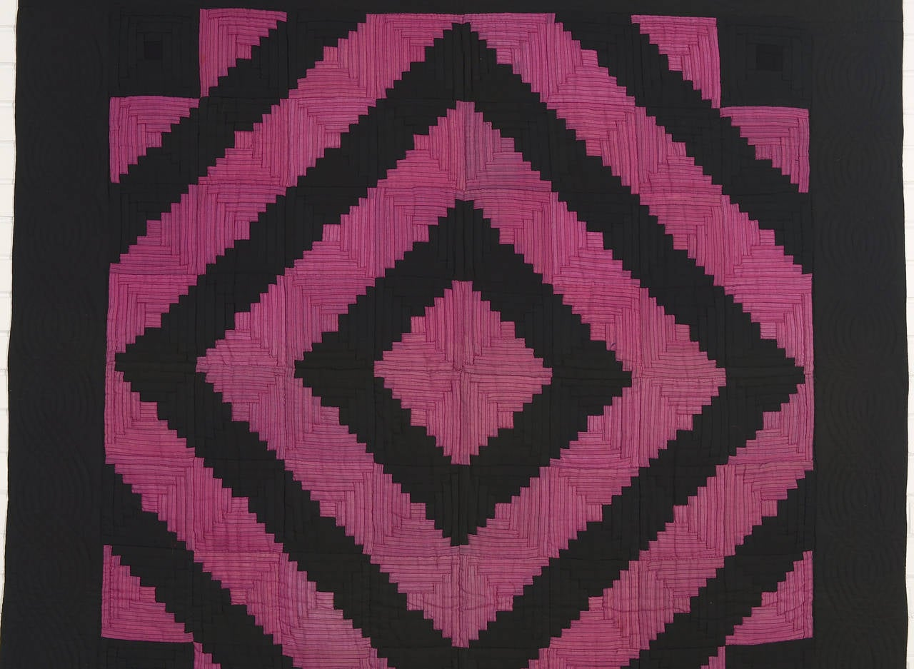 While the barnraising log cabin is a very quilt traditional pattern, this example looks far more modern than one expects from the late 19th century when it was made. The magenta fabric has a thin black stripe that perfectly ties in with the solid