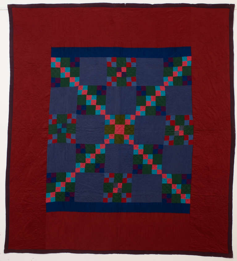 This Lancaster County Amish four patch in a nine patch quilt is brilliantly arranged.The maker used the same colors throughout but placed them so as to create the unusual overall X pattern. This might be a one of a kind. The solid color blocks and