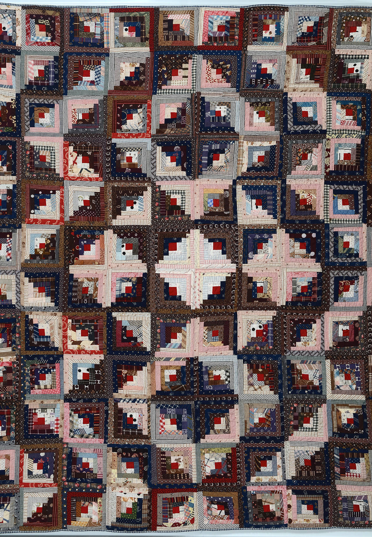 This unusual log cabin quilt is actually three different patterns. There is a streak of lightning surrounding the star center as well as a light and dark pattern above and below the star. It is extraordinary to realize that the same log cabin block