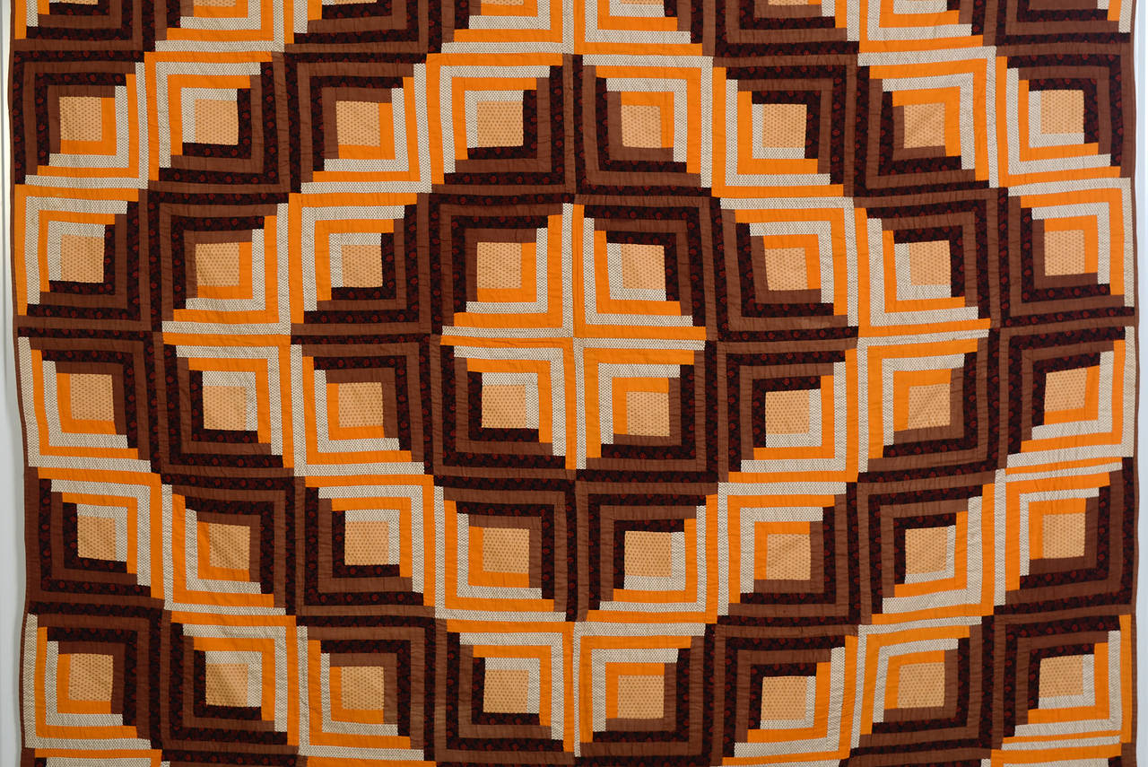 This Classic barn raising log cabin quilt is done with an unusual color palette. Solid and printed oranges and browns are beautifully combined. The quilt is in excellent condition. Measurements are 82