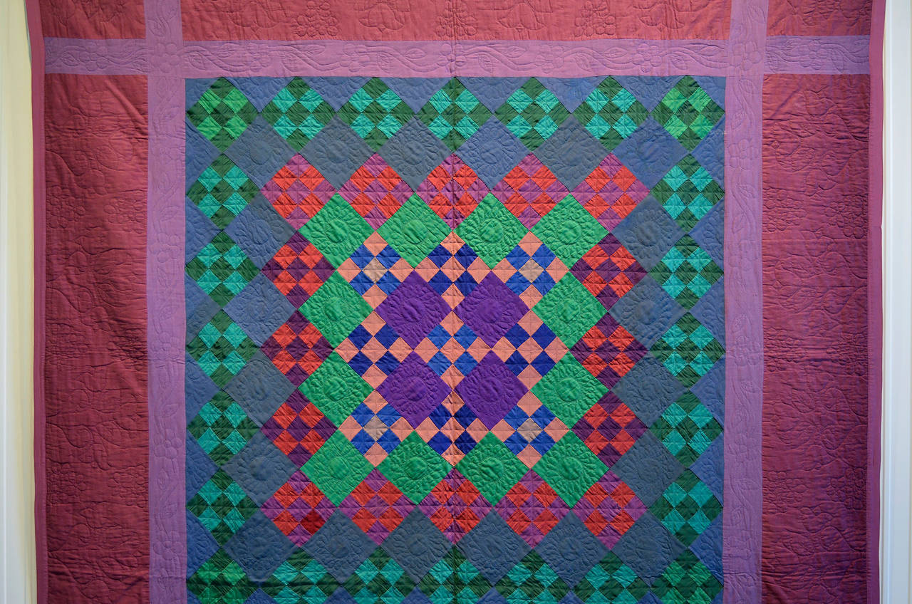 This stunning Nine Patch variation has all of the bells and whistles one hopes for in a Lancaster County Amish quilt. The same Nine Patch on point blocks are used throughout but the use of color creates a center medallion. The colors are the classic