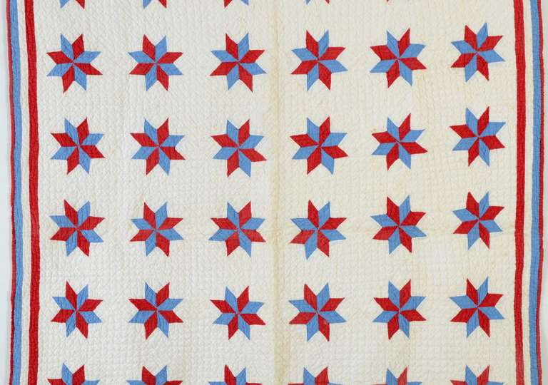 Red and blue LeMoyne Stars crib quilt made even more charming by the quilted inscription