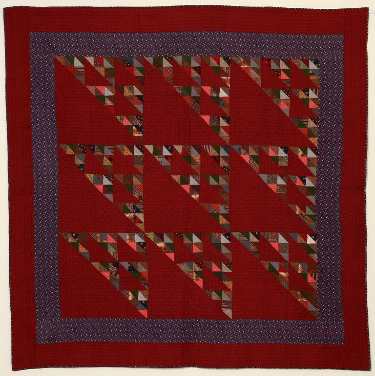 This birds in the air quilt is done with a lush combination of saturated colors. The red printed ground combined with the purple printed border are fabrics not often seen. They combine beautifully and work well with the prints of the small