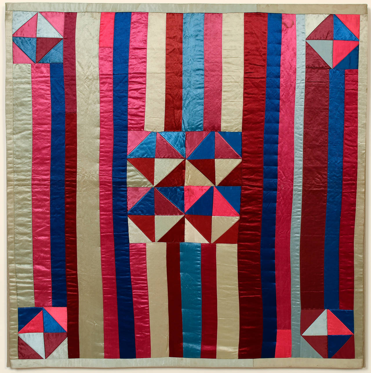 This hourglass crib quilt on a striped ground is an unusual but very successful pairing of patterns. The choice of satin fabrics is also out of the ordinary. It is in pristine condition and is mounted on a stretcher measuring 31