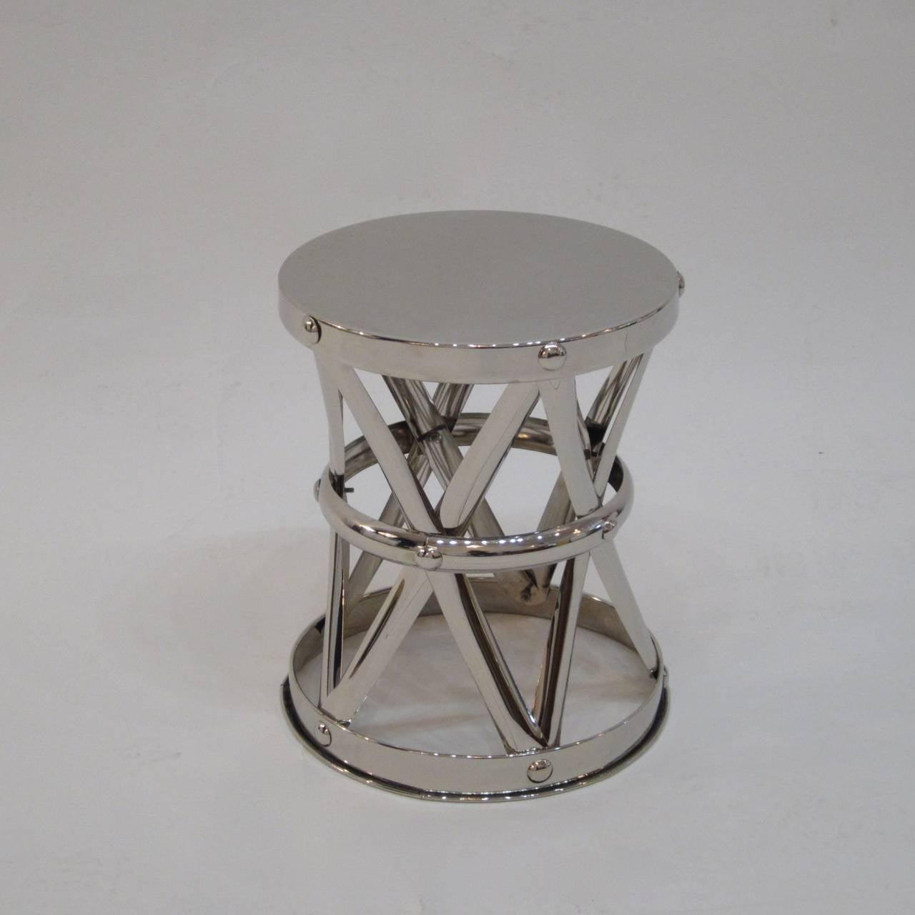 Classic X-frame criss-cross garden stool in nickeled brass. A great side table to hold a drink or magazine.