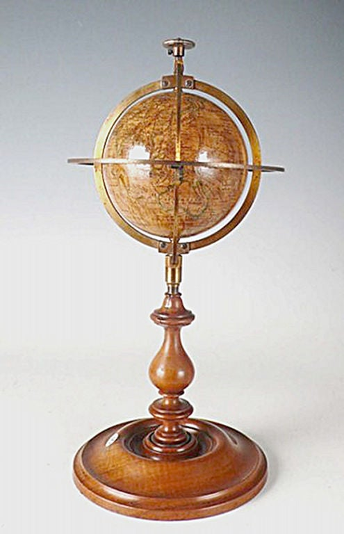 A rare and small terrestrial globe, papier maché, caged into a brass armillary structure, with tall foot and mahogany wood base. France, Paris, signed Delamarche.