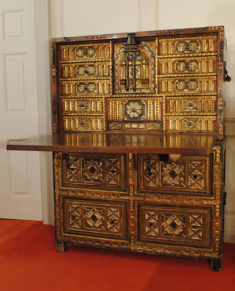 An outstanding example of a 17th century walnut and bone vargueno with painted and gilded decoration, the fall front with good original metal work and the cabinet standing on a fitted chest.