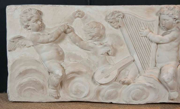 A beautifully carved 19th century plaster frieze coming from an old Connecticut estate depicting scenes of cherubs playing musical instruments.