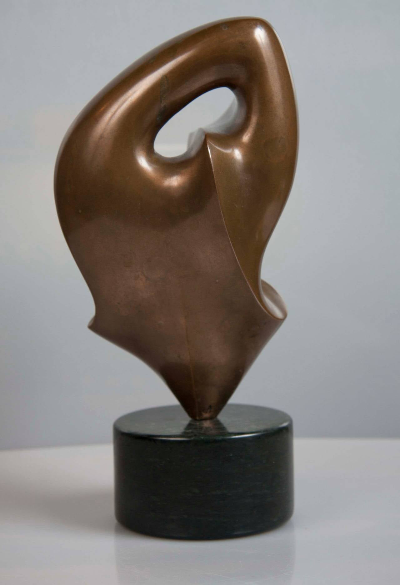 An abstract bronze sculpture by Swiss artist Antoine Poncet. (b. 1928) mounted on round marble base. Height of sculpture alone: 7 inches. Overall height is nine inches.