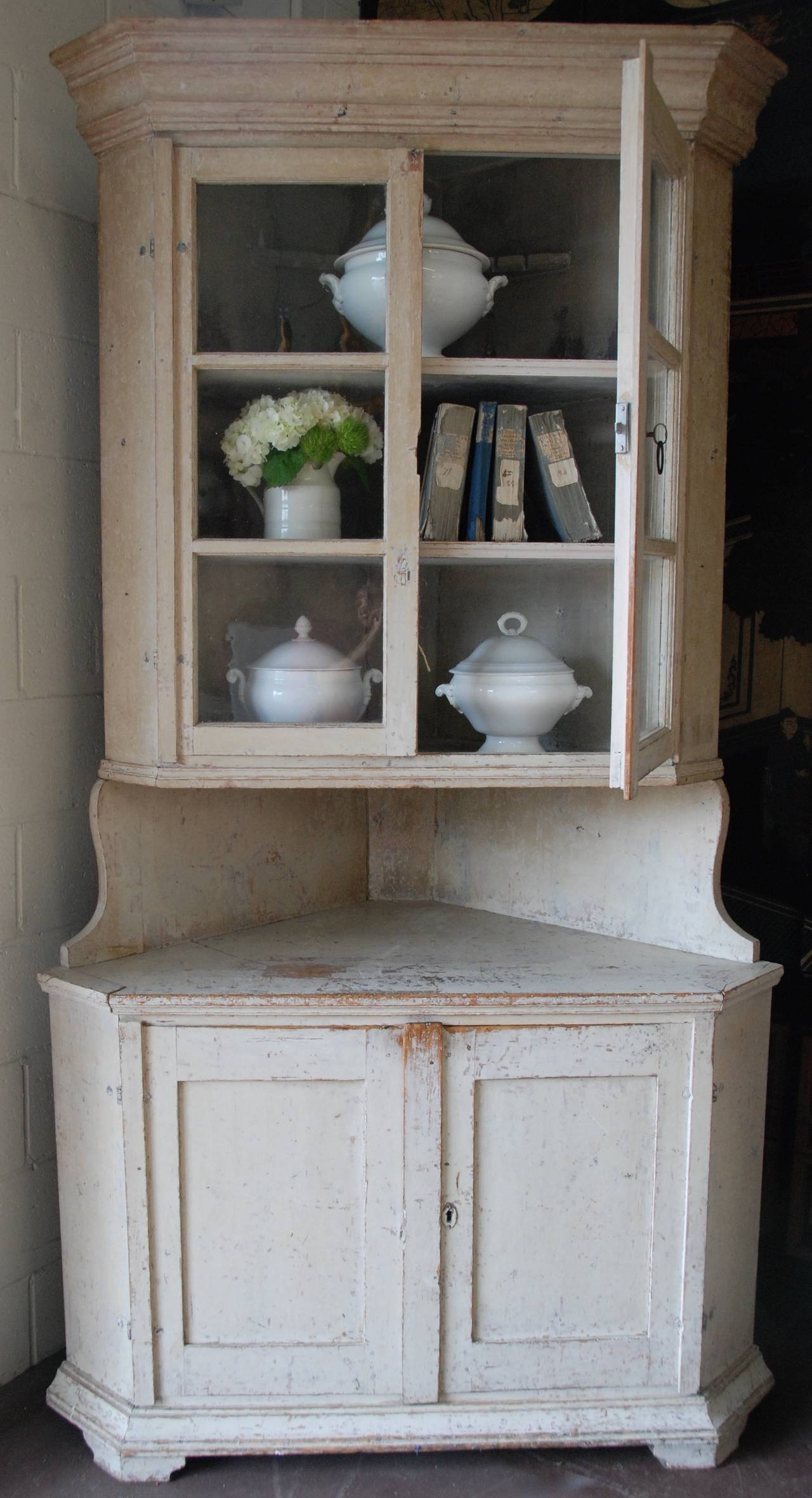 Lovely 18th century Swedish corner cabinet scrapped down to the original cream/white color. Original glass in paneled doors.