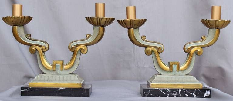 Gorgeous pair of lamps with two scrolled lights each, in a pale blue-green and gold patinated bronze. Resting on a black marble base.  USA electrified.