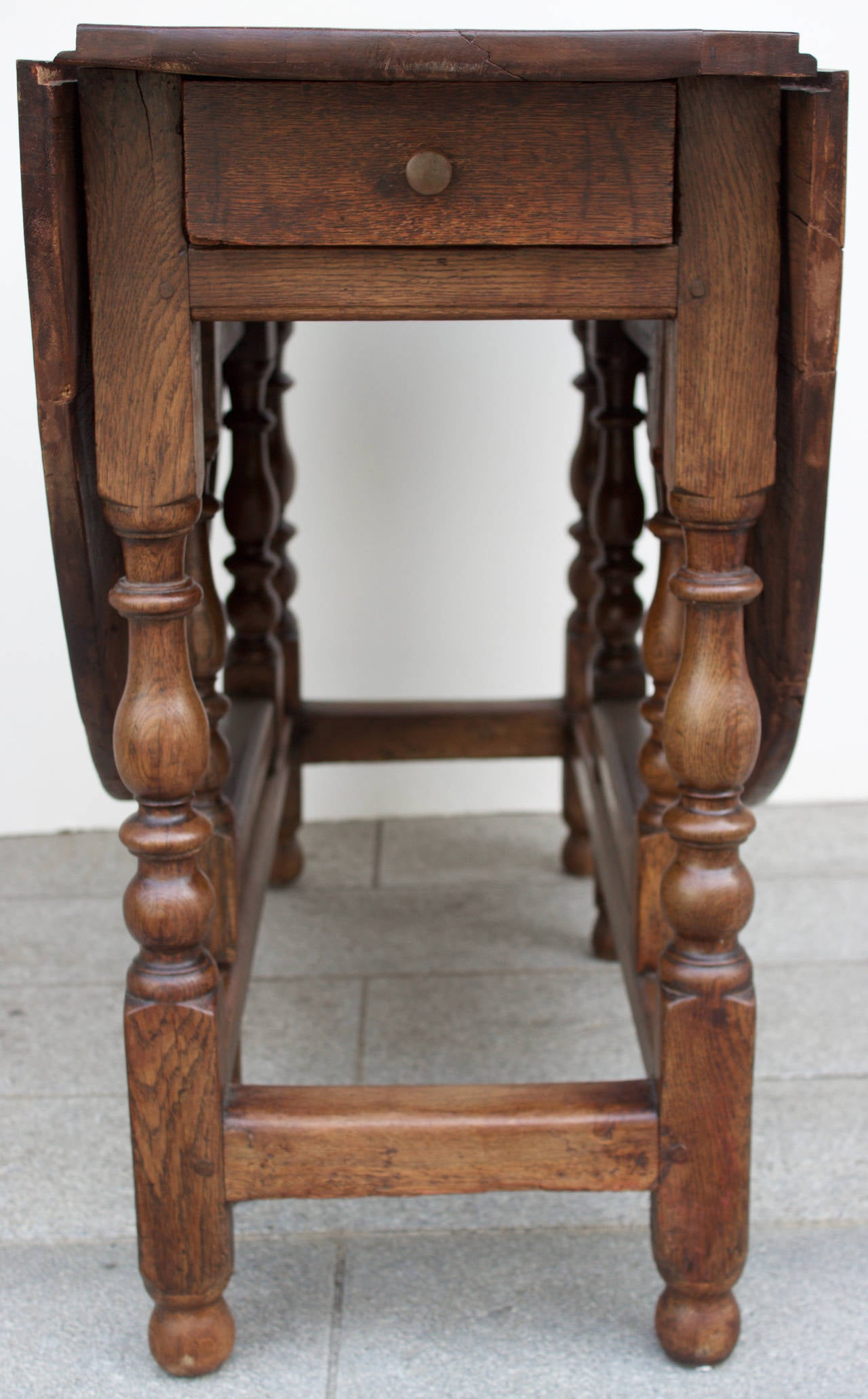 Fine French gateleg table entirely handmade with twin flaps and one drawer. Beautifully turned feet and lovely patina. Can be used as dining table, breakfast table, center table or behind a sofa.