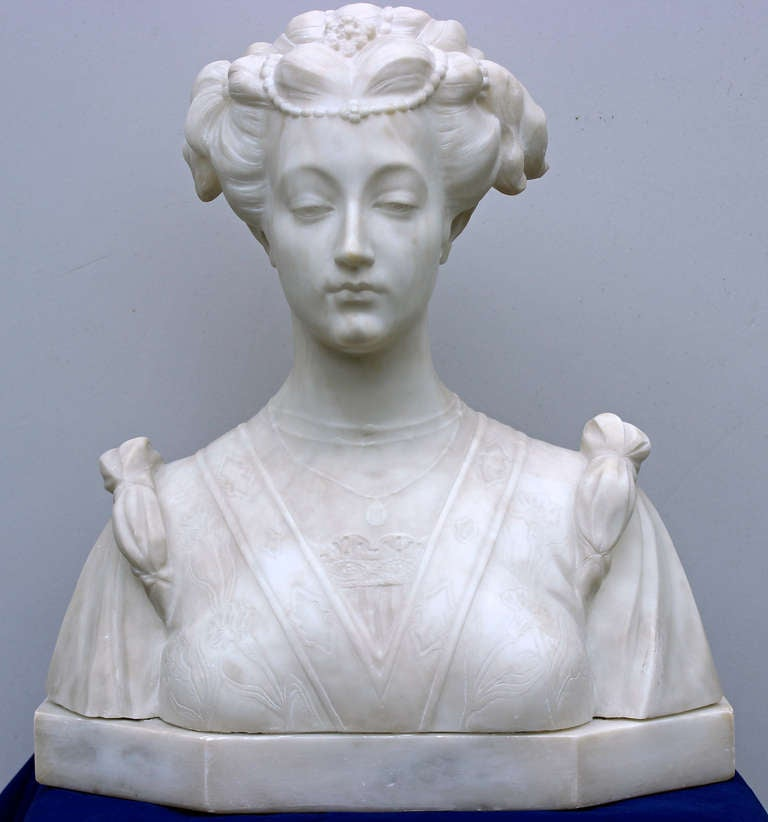 Great rendering by the artist of the beauty and the facial expression of this women apparently lost in thoughts. Also nice detailed sculpture of the pearl strewn hair, the three rows little necklace chain with a pendant marked M , the carving of the
