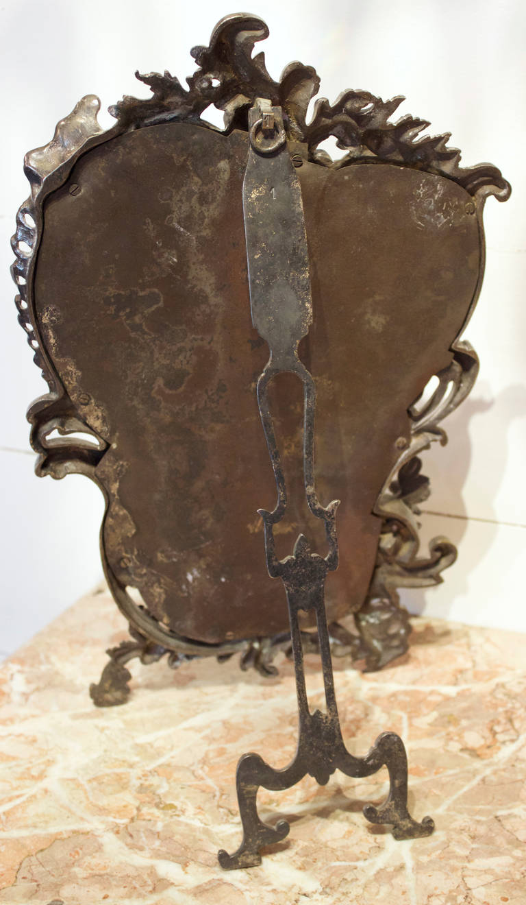 Napopleon III style violin shaped table mirror with a silvered bronze rocaille decor of scrolled acanthus leaves, little flowers and bottom left a Mythological Animal called