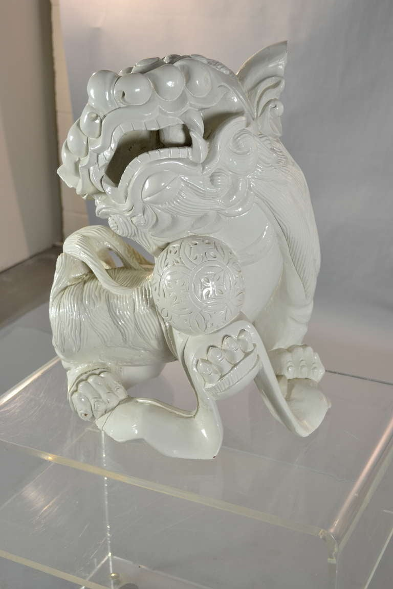 Lare carved wood foo dog seems to be carved from one piece of wood --with reticulated ball inside the mouth. Gloss painted finish.
