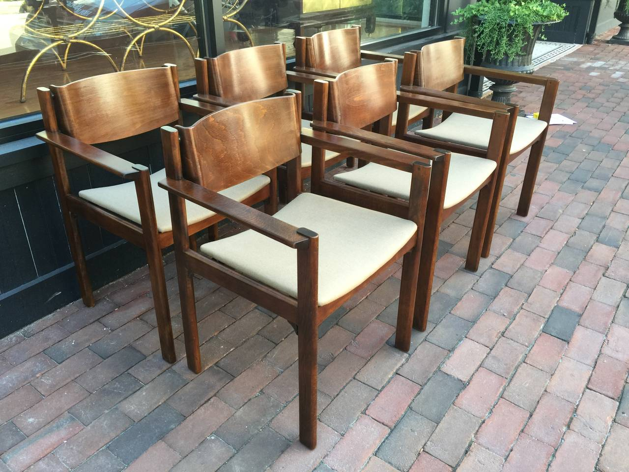 Set of six bent mahogany arm chairs, retailed by Harvey Probber, each one with flat bar arms and solid ribbon back and newly upholstered seats. The arm height is 25
