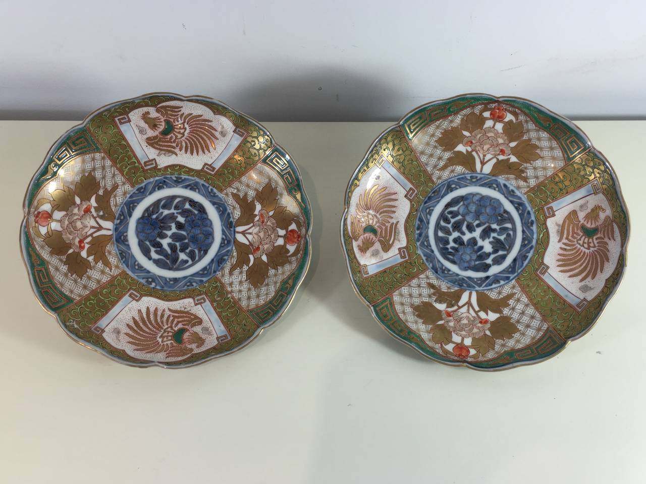 Pair of Fukagawa Imari Plates, of circular scalloped form and unusual decoration in green, gold and blue palate. With blue underglaze mark, and decorated exterior rim