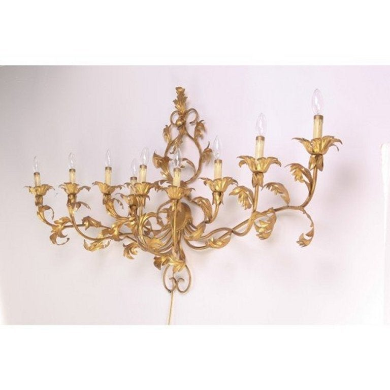 1960s Monumental 9 Arm Mid Century Gilded Sconce. Still retains original gilded tag that reads Made in Italy. Gilt metal and iron. Cord with on/off switch plugs into wall outlet and lights all 9 arms. This is a very large 5ft sconce with 62