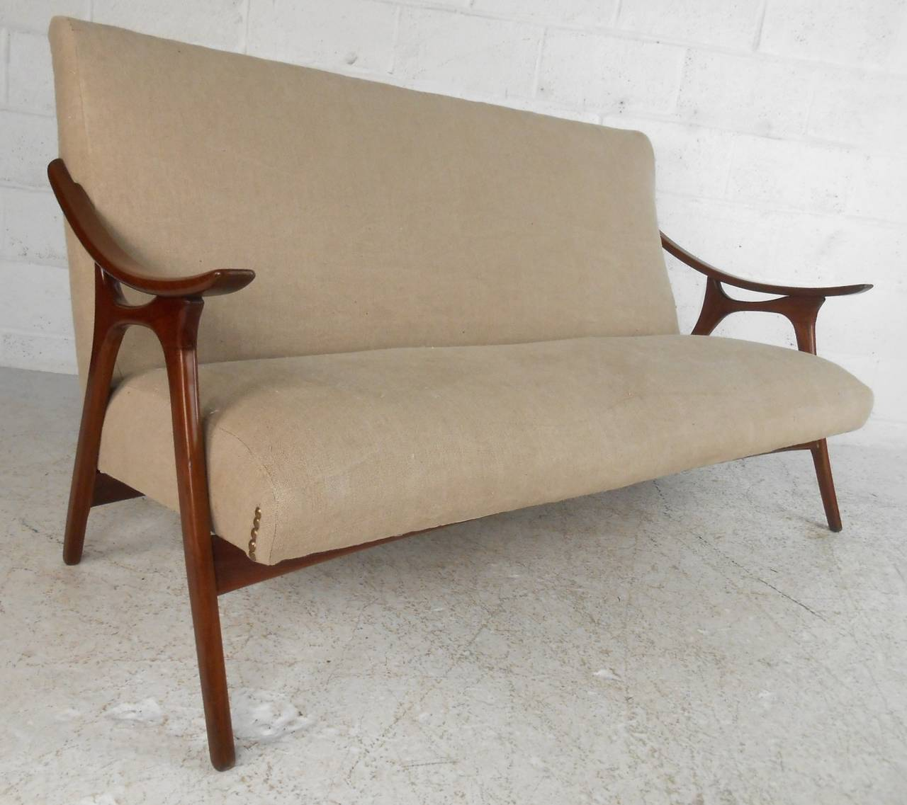 This unique midcentury sofa features stylish curved armrests, original studded upholstery, and a unique finish. Please confirm item location (NY or NJ).