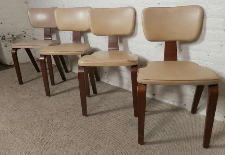 Four vintage chairs by Thonet with classic angled frames. Crafted of bent wood that shows off an lovely sculptural design. The seat and back rest are covered in a cream white vinyl. Once restored these will pop back to life!  (Please confirm item
