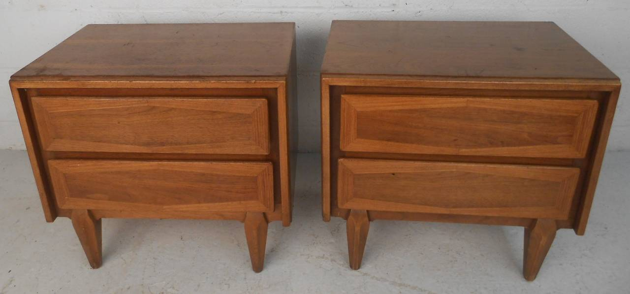 This gorgeous pair of vintage modern end tables feature two hefty drawers and sturdy tapered legs. Sleek two-tone design with unusual wood grain running in different directions on the drawers. This fabulous pair of night stands make the perfect