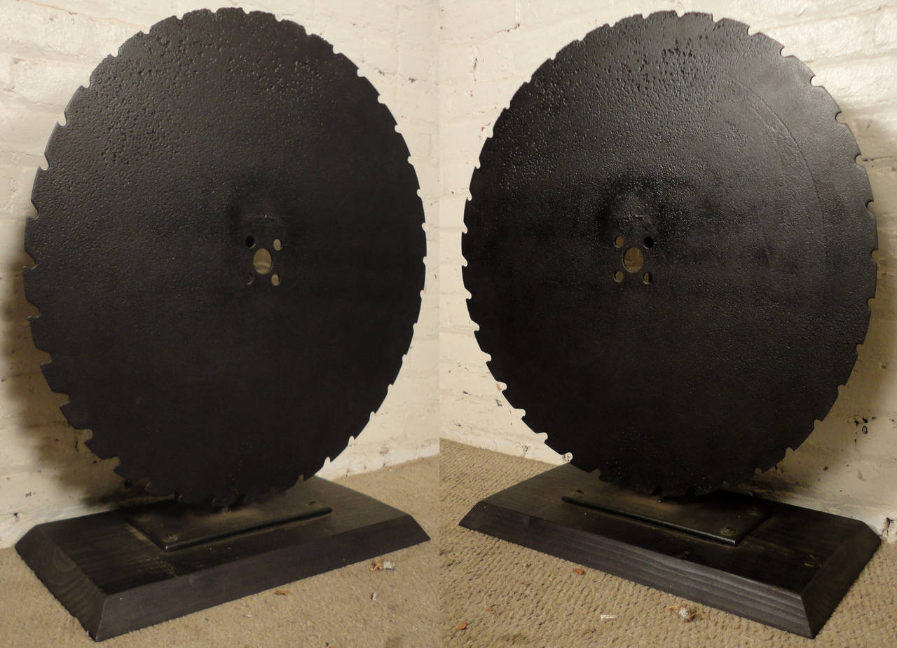 Decorative iron mounted saw wheels. Impressive black painted saw blades on a matching wood base, make for a striking piece of art.