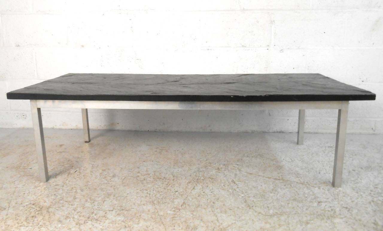 This unique slate top midcentury coffee table features a hefty piece of textured slate set upon a sturdy metal base. Unique vintage piece with Industrial charm provides a wonderful centrepiece for any seating situation. Please confirm item location