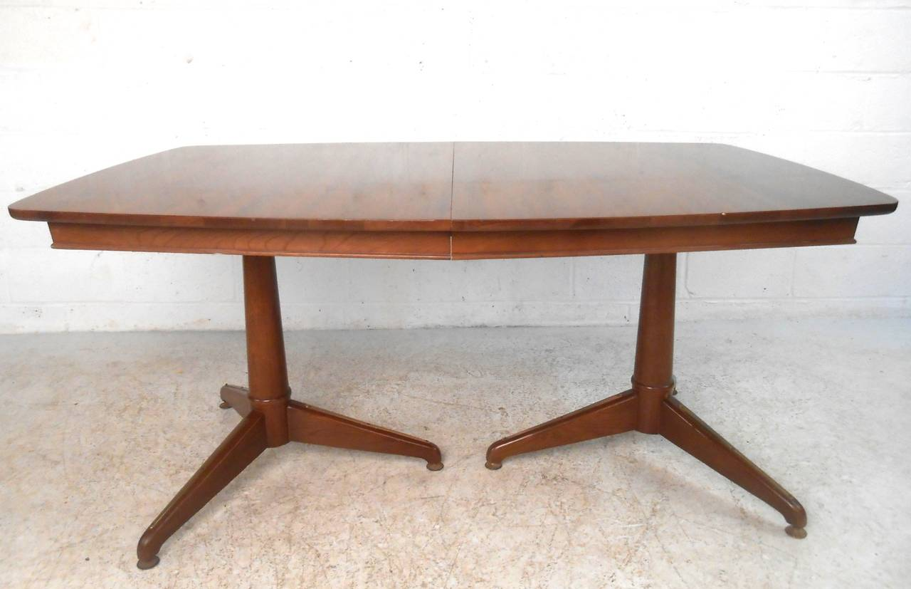 This unique midcentury walnut dining table is set on two sturdy industrial style metal pedestal legs. Additional leaf extends width from 63.5