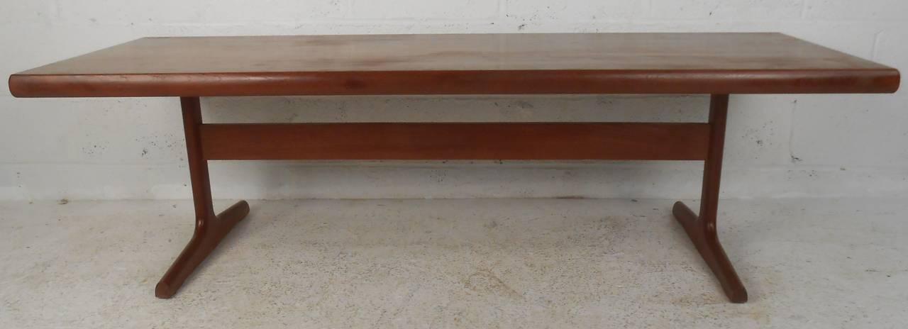 Danish modern trestle style coffee table in teak. This sleek mid-century modern coffee table has a large rectangular top and sturdy sled legs. The beautiful teak wood grain and smooth edges make this table the perfect addition to any modern