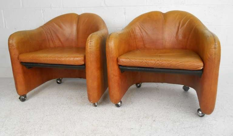 Pair of leather distressed Italian club chairs with beautiful patina, shapely barrel backs, and casters make a striking vintage modern addition to home or business seating. Please confirm item location (NY or NJ) with dealer.