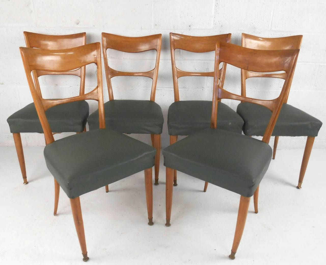 This set of six sculpted back dining chairs feature wonderful curved backs, as well as tapered and brass capped feet. Please confirm item location (NY or NJ).