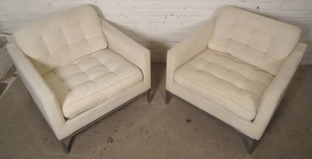 Vintage pair of comfortable armchairs designed by Knoll Associates. Chairs feature off-white tufted upholstery and sleek polished chrome legs. Both chairs come with optional arm protecting covers.   (Please confirm item location - NY or NJ -