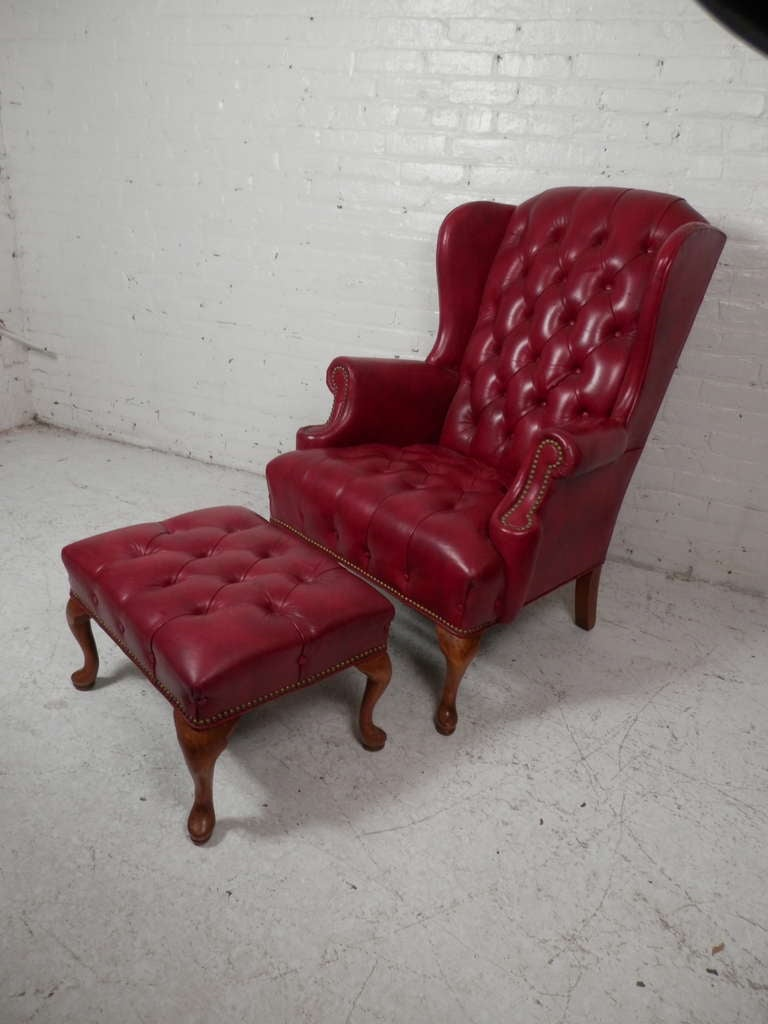 High back reading chair complete with rolled arms, deep wings, tufted back cushion and brass nail heads. Very good wear and patina to the leather.