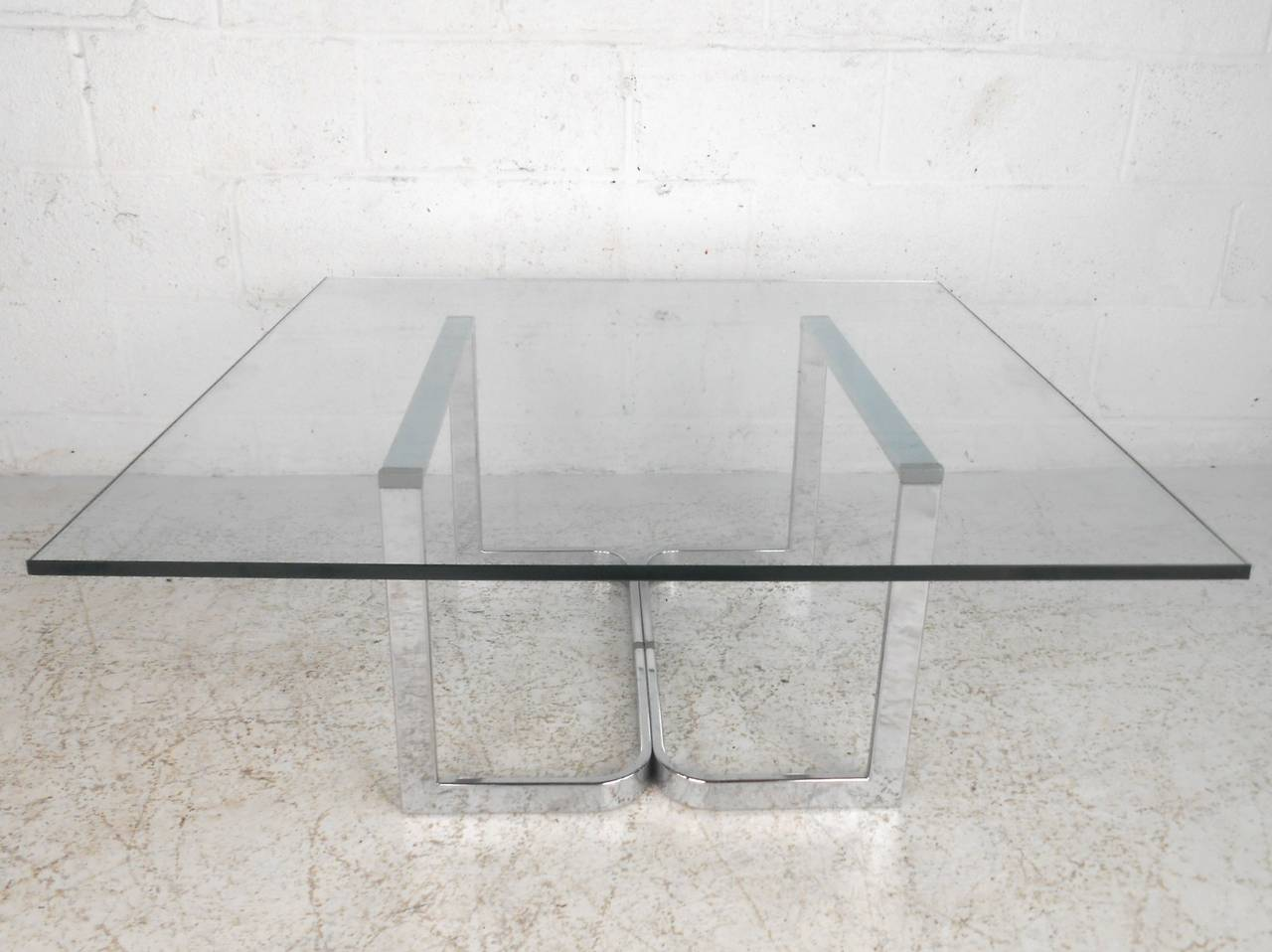 This unique midcentury coffee table makes a sturdy and stylish centre table for any seating area. The heavy flat bar chrome frame comfortably supports the large square glass top. Wonderful lines and subtle style combine for a wonderful example of
