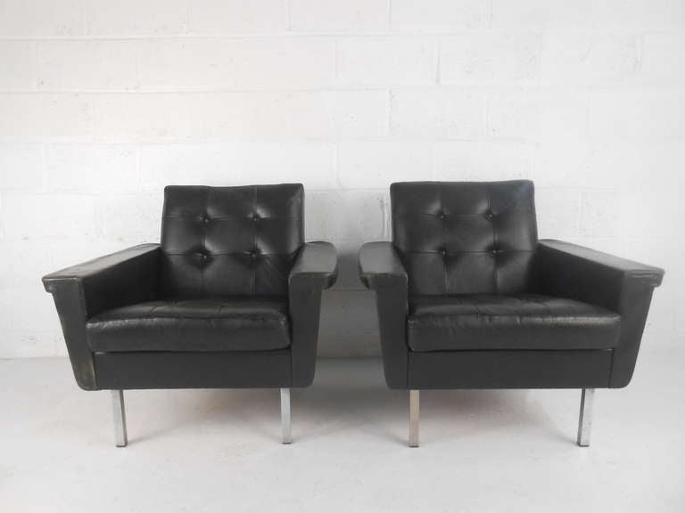 Classic Mid-Century styling leather armchairs with wide arms, tufted backs and simple square-tube metal legs. Danish influences. Comfortable with normal-use wear to leather on arms and edges. Please confirm item location (NY or NJ) with dealer.