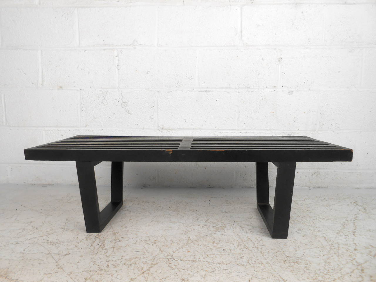 This midcentury slat bench by George Nelson features a compact size and ebonized finish which offer a bold modern accent to any home or office space.   Please confirm item location (NY or NJ) with dealer.