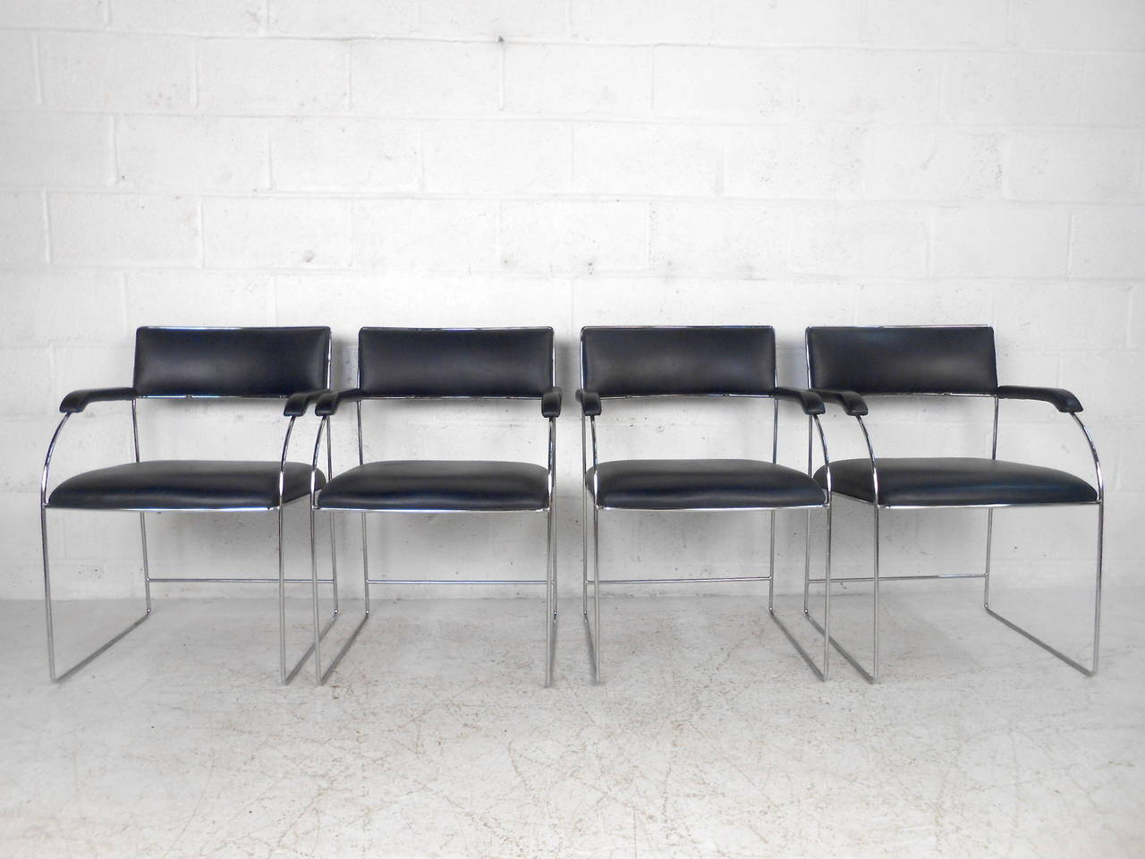 This set of midcentury dining chairs feature comfortable blue vinyl upholstery and a sturdy chrome tubular frame. A wonderful chrome rod frame with sled legs and rounded arm rests with padding. Ideal matching set of four chairs makes a stylish