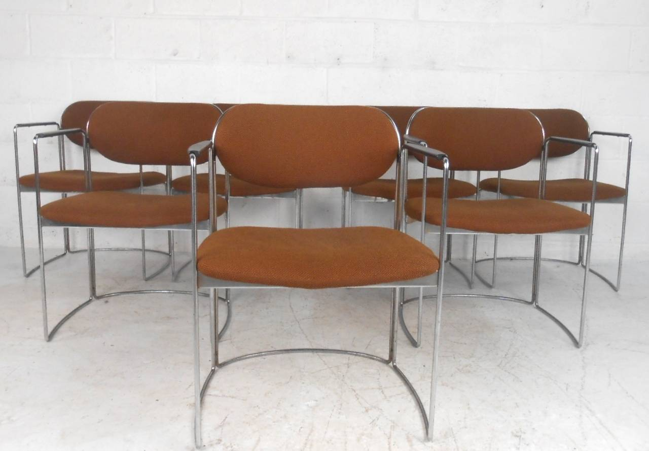 This set of seven vintage armchairs offer wide comfortable seats complete with sturdy chrome frames and molded armrests. A sleek design that boasts a chrome rod frame with an ellipse shaped base. Vintage fabric is intact, perfect matching set for