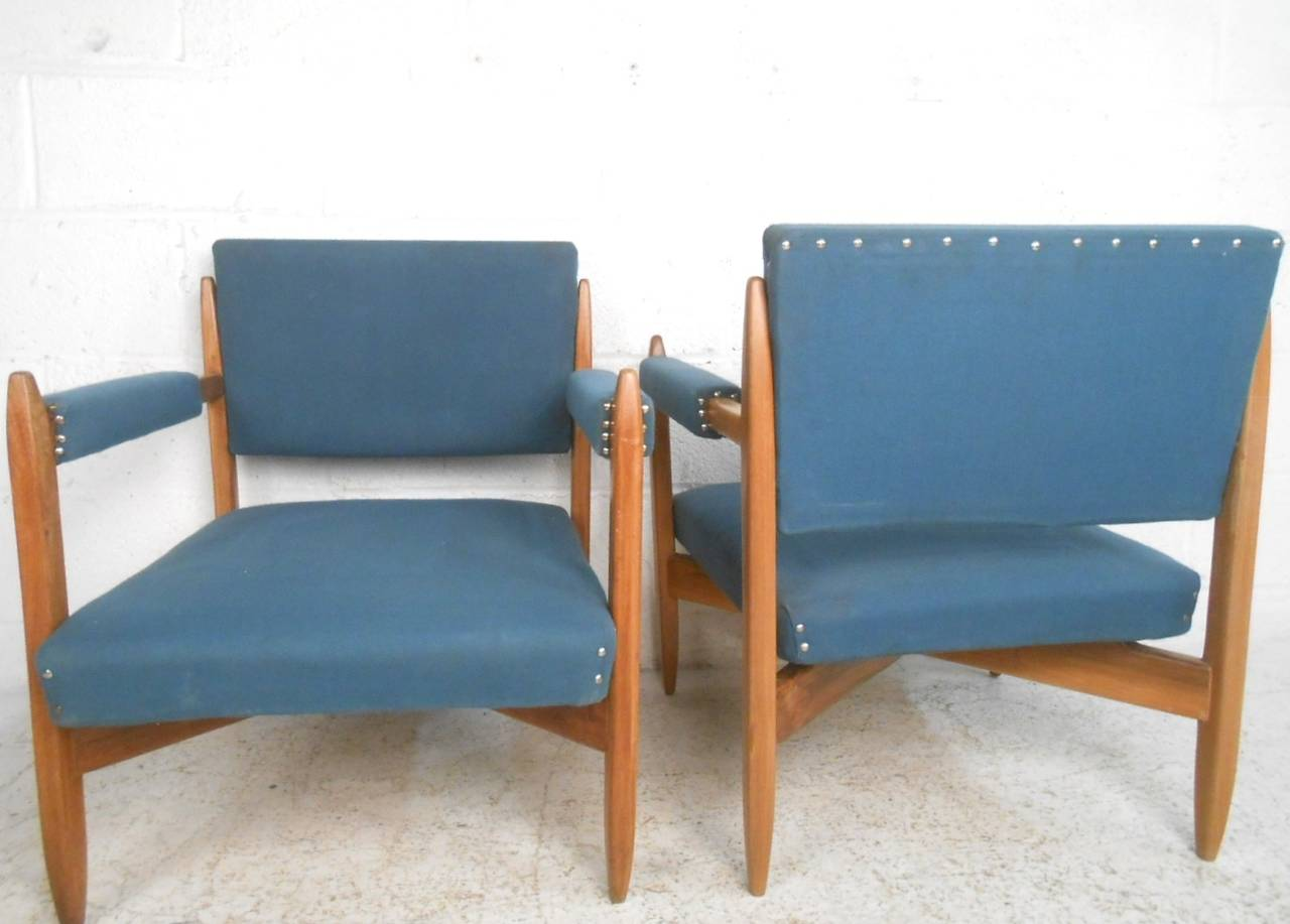 This comfortable pair of midcentury lounge chairs features unique design including wonderful toothpick style tapered frame. The elaborate plush blue upholstery and vintage walnut finish compliment each other. Sturdy and stylish, with padded armrests