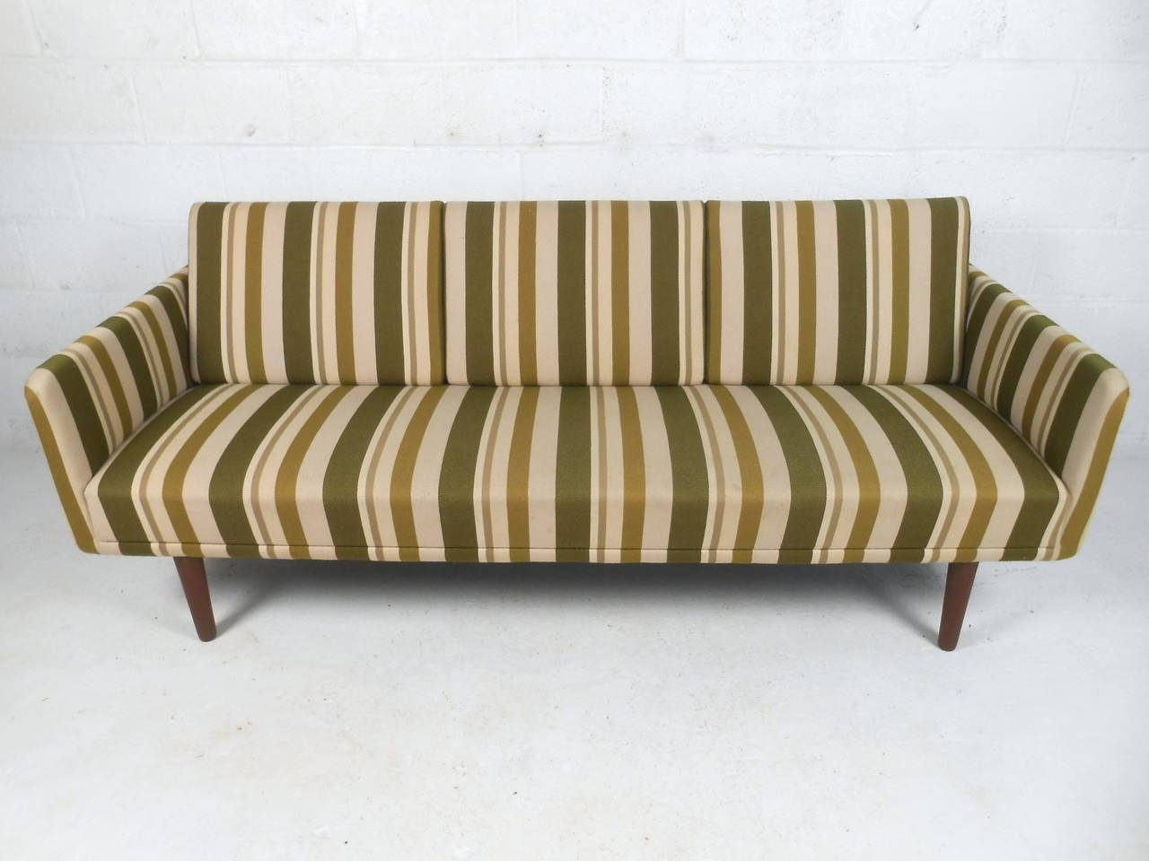 This beautiful Mid-Century sofa combines simple yet elegant lines with striking vintage upholstery. Unique yet subtle vintage Danish design makes this a wonderful addition to any modern interior. Please confirm item location (NY or NJ).