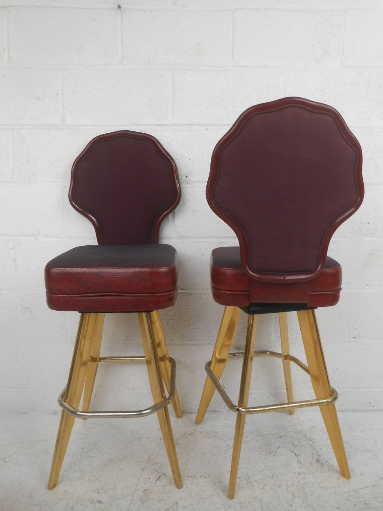 Mid-Century Modern set of swivel stools with a great vintage Las Vegas vibe. Polished brass legs that taper down, vinyl and cloth seating with eggplant color, and sculpted backs.  (Please confirm item location - NY or NJ - with dealer).
