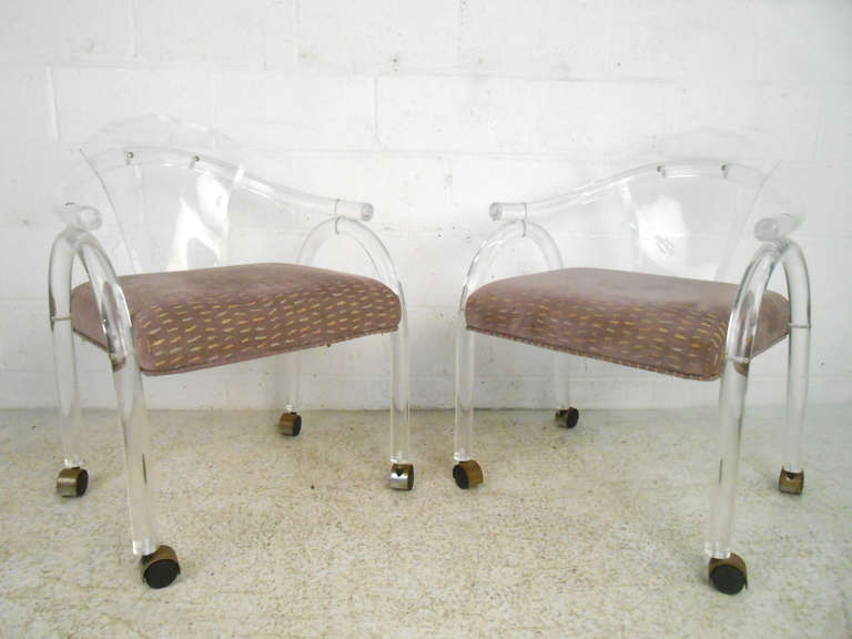 Uniquely shaped pair of lucite side chairs on casters with upholstered seats. Please confirm item location (NY or NJ) with dealer.