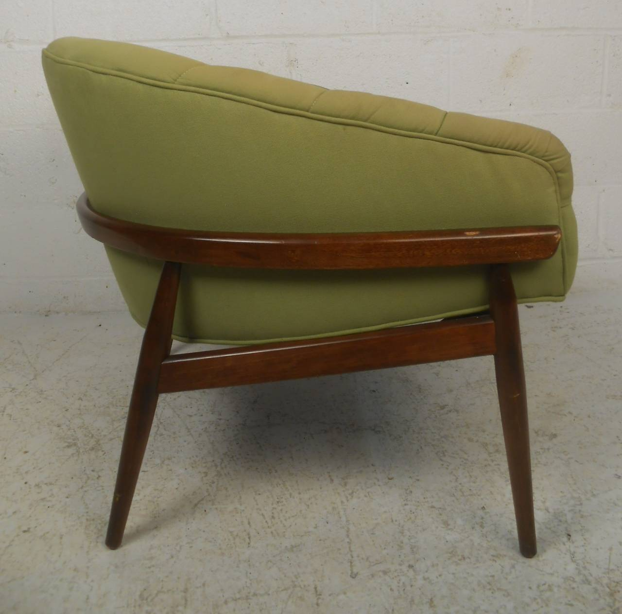 Mid-Century Modern walnut frame lounge chair with barrel back rest and tufted green upholstery. A wide design with overstuffed seating ensuring maximum comfort. Quality craftsmanship that boasts a sculpted dark walnut frame with tapered and splayed