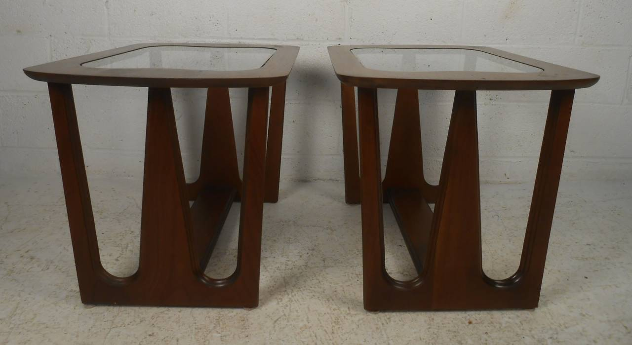 Sculptural pair of Mid-Century Modern walnut end tables with glass tops. Nicely proportioned and Classic 1960s styling, they can be used as lamp tables or used together as a smaller scale coffee table. Please confirm item location (NY or NJ) with